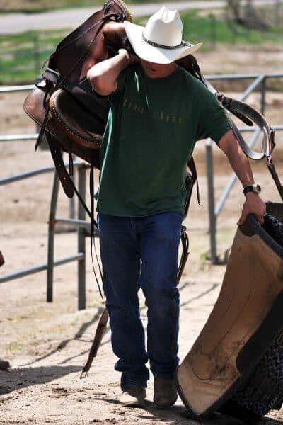 Horse trainer carrying saddle and saddle blanket over his shoulder