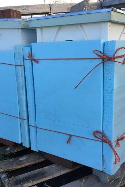 Bee boxes wrapped in insulation for winter