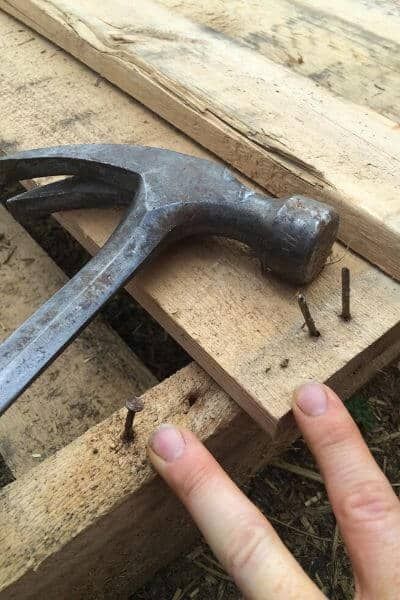 pulling nails out of a pallet to make it useful for building